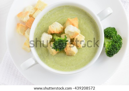 Fresh broccoli cream soup with croutons on white table, flat lay. Selective focus