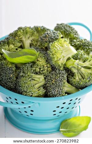 Fresh broccoli florets in blue colander on white - stock photo