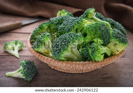 Fresh broccoli in basket on wooden table - stock photo