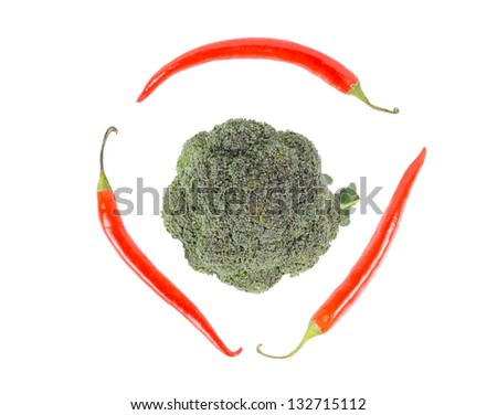Fresh broccoli surrounded by three red chili peppers, on white background, high angle - stock photo