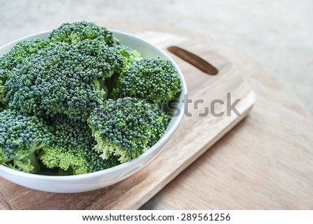 Fresh broccoli vegetable in white bowl on wooden table - stock photo