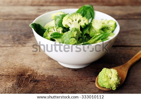 Fresh broccoli with spinach in bowl on wooden table close up - stock photo