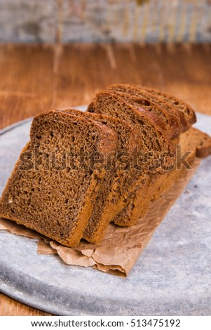 fresh brown pieces of bread on wooden background in studio