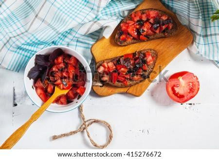 fresh bruschetta on a wooden cutting board - stock photo