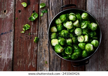Fresh brussel sprouts over rustic wooden texture. Top view. - stock photo