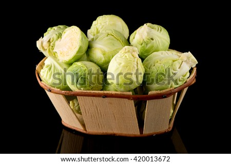 Fresh brussels sprouts and wooden baslet isolated on black background. - stock photo