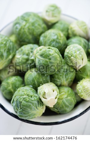 Fresh brussels sprouts in an enameled bowl, view from above - stock photo
