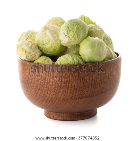 Fresh brussels sprouts on brown wood bowl isolated on white background.