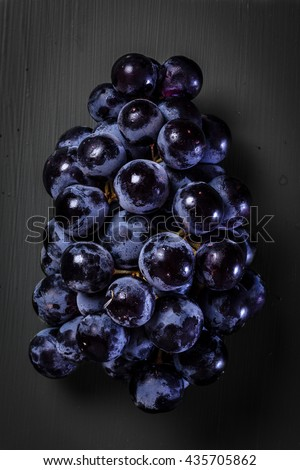 Fresh bunch of grape and water drops on black background  - stock photo