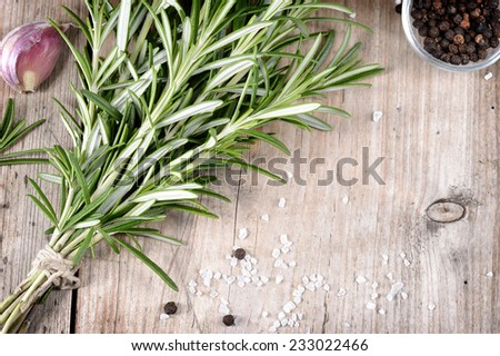 Fresh bunch of rosemary, garlic, pepper and salt on wooden table. Aromatic evergreen herb, many culinary - roasted meats. Copyspace. - stock photo