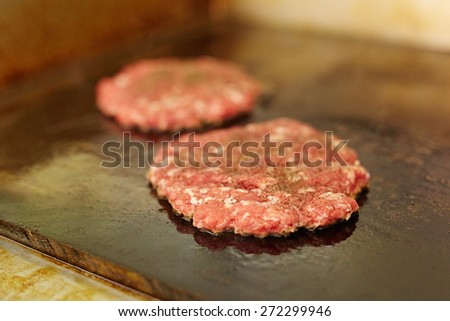 Fresh burger patties seasoning on top frying next to each other on a grill with  - stock photo