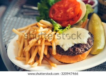 Fresh burger with cheese and french fries outdoors - stock photo
