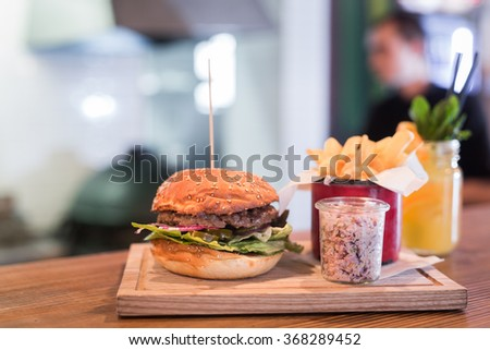 Fresh burger with french fries, salad and lemonade on wooden table. - stock photo