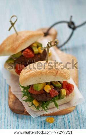 Fresh burgers with salsa (cherry tomato, avocado, corn) - stock photo