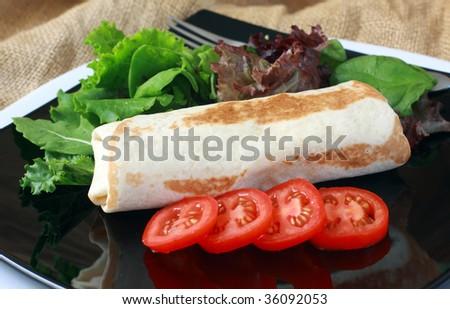 fresh burrito with salad on black platter and tomato - stock photo