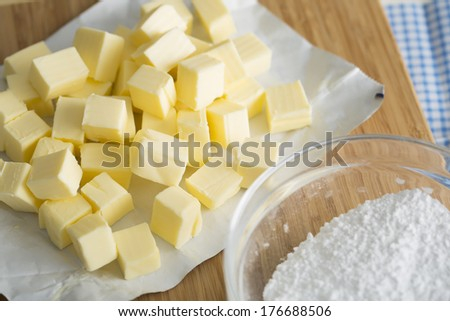 Fresh butter cubes on cutting board with bowl of flour. - stock photo