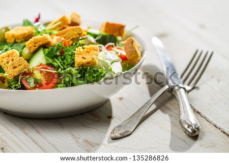 Fresh Caesar salad on old white table - stock photo