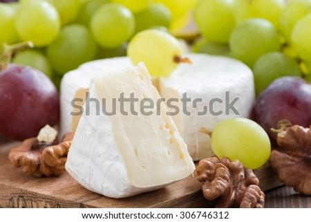 fresh camembert, walnuts and fresh grapes, horizontal - stock photo