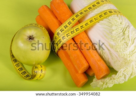 fresh carrot, apple, centimeter and sprouts on a green background