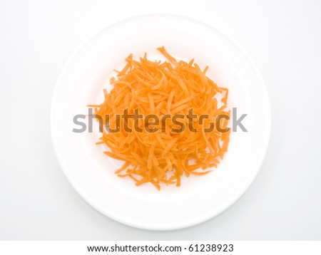 Fresh Carrot grated for a delicious salad on white plate.