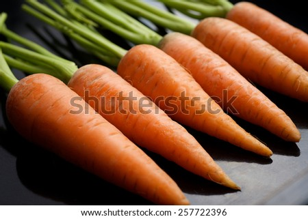 Fresh carrots on a black background - stock photo