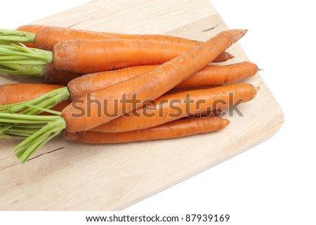 fresh carrots on cutting board - stock photo