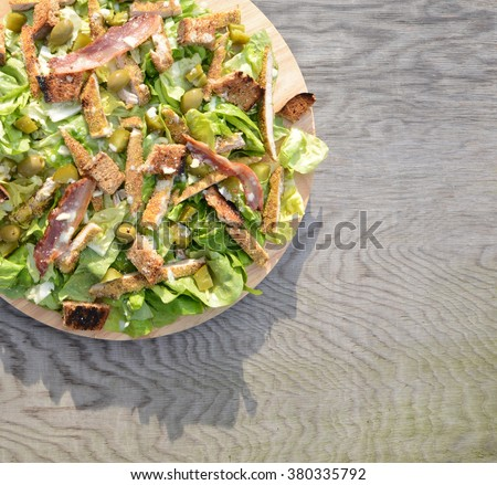 Fresh Ceaser salad on wooden table - stock photo