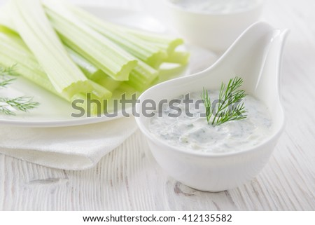 Fresh celery sticks with yogurt dip on white wooden background, selective focus