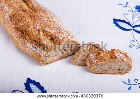 Fresh cereal baguette on white cloth. Sliced bread. - stock photo