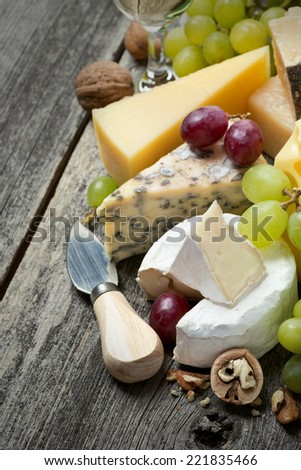 fresh cheeses, grapes and walnuts on a wooden background, vertical - stock photo