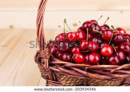fresh cherries in a wicker basket on the wooden background