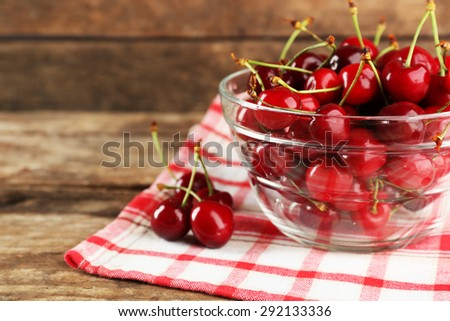 Fresh cherries in glass bowl with napkin on wooden background