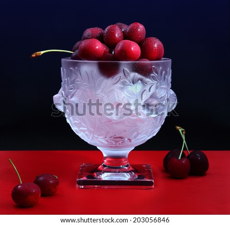 Fresh cherries on ice/Cherries on ice/Fresh juicy cherries on ice in a beautiful crystal bowl. Shot in studio. - stock photo