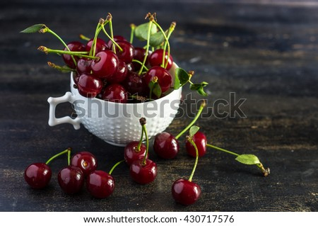 Fresh cherry berries on rustic wooden table and vintage background - stock photo