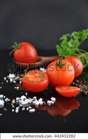 Fresh cherry tomato with spice on black background - stock photo