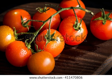 Fresh cherry tomatoes on a branch. Tomatoes with water drops - stock photo