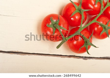fresh cherry tomatoes on a cluster over rustic wood table - stock photo