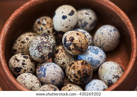 Fresh chicken eggs and quail eggs at wooden plate closeup - stock photo