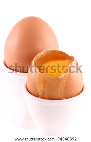 Fresh Chicken eggs shell on egg cups with one opened showing yellow yolk and Egg white dripping