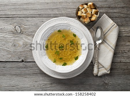 Fresh chicken or beef soup on wooden background overhead shoot - stock photo