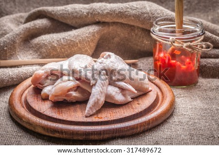 Fresh chicken wings on wooden board. Shallow depth of field. - stock photo