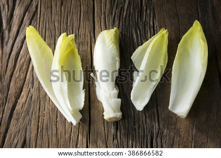 Fresh Chicory Salad leaves placed on a rustic wooden table. - stock photo