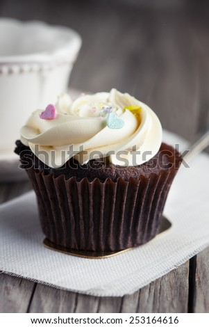 Fresh chocolate cupcakes decorated with creamy vanilla cream on old wooden background, selective focus - stock photo