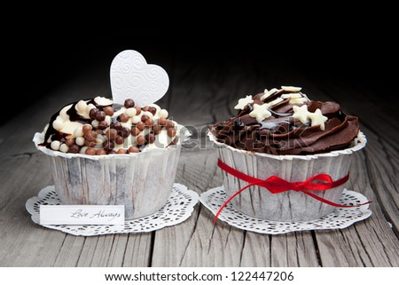 Fresh chocolate cupcakes decorated with white heart and a red ribbon on a wooden floor background - stock photo