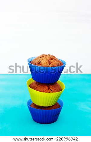 Fresh chocolate muffins in bright silicone cupcake holders. Concept of good morning and tasty food. - stock photo