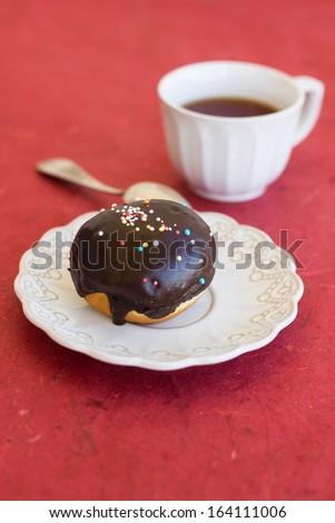 Fresh chocolate sufgniya (donut) on a napkin with a cup of tea - stock photo