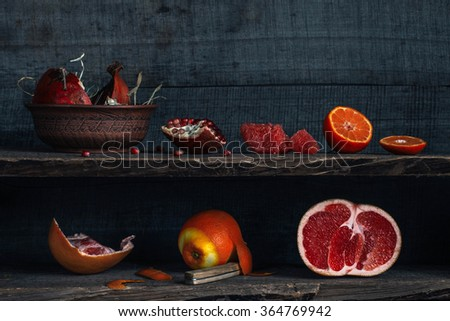 Fresh citrus and pomegranate on the old wooden shelves, rustic style - stock photo