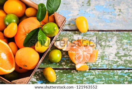 Fresh citrus fruits in the wooden box on rustic table - stock photo