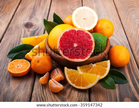 Fresh citrus fruits on a old wooden table - stock photo