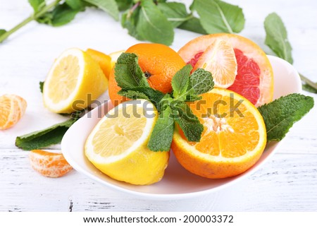 Fresh citrus fruits with green leaves in bowl on wooden background - stock photo